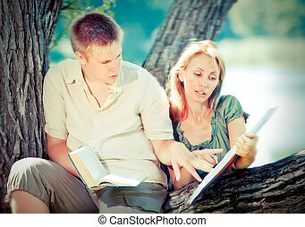 Young guy and girl with books on the nature near lake,with a retro effect