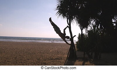 Young guy demonstrates human flag at sea beach. Athletic man doing gymnastics elements on palm tree at exotic ocean shore. Male sportsman performs strength exercises during workout. Training outside