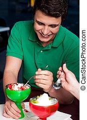 Young guy enjoying tempting dessert