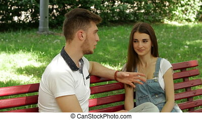 young guy flirts and amuses the girl in the Park on a bench