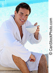 young guy having coffee at edge of swimming-pool