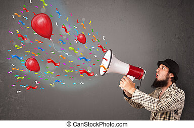 Young guy having fun, shouting into megaphone with balloons