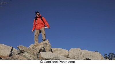 Young guy hiker is happy about his ascent on the top of the cliff. Winner is lifting his hands at the sky background.