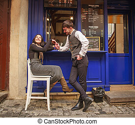 Young guy in classic suit meets and flirting girl near city cafe in old town