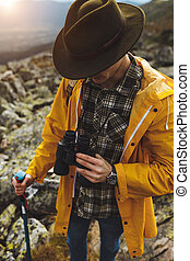 young guy in shirt, yellow coat, green hat has problems with binocular