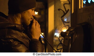 Young Guy is Calling and Speaking in Telephone Booth at...