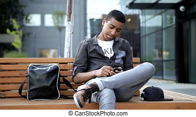 Young guy is chatting a message for his classmates in his mobile phone . He is sitting on a beanch in front of his university
