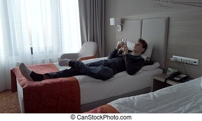 Young guy is lying on a bed in a hotel room