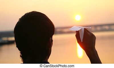 Young guy launch paper plane against the sea during sunset with sun flare and reflections in the water, as in childhood. Videw from his back. 3840x2160
