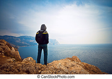 Young guy looking into the distance at sea