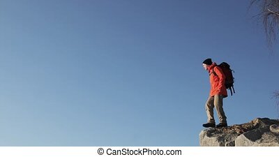 Young guy on the peak of the cliff is raising his hands at the sky background happy about his ascent.
