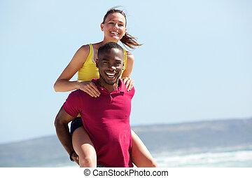 Young guy piggybacking his girlfriend