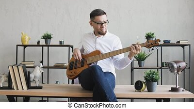 Young guy playing guitar enjoying it sitting on office table, camera in motion.