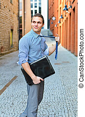 Young guy posing with a laptop on the street.