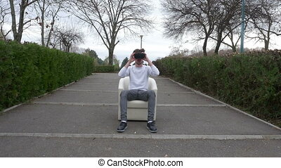 Young guy sitting an armchair in a park puts on VR headset and enters a virtual reality world