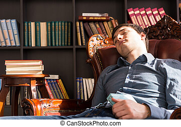 Young Guy Sleeping on the Chair Holding a Book