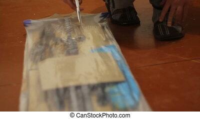Young guy unpacks ironing board. Slow motion