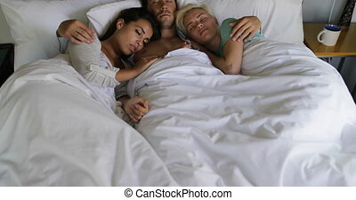 Young Guy Waking Up In Bed Embracing Two Women, Beautiful Girls And Man In Bedroom Morning