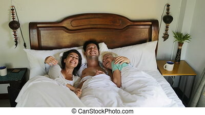 Young Guy Waking Up In Bed Embracing Two Women, Beautiful Girls Kiss Man In Bedroom Morning