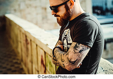 city portrait of a young guy with a beard, tattoo and glasses on the street