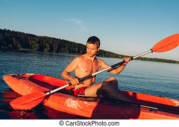 young guy without t-shirt is swimming on a red kayak with a paddle in his hands, close-up