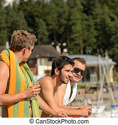 Young guys at beach drinking beer - Young guys holding...