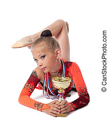 young gymnast lay with medal and prize cup - young gymnast...