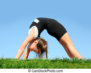 Young gymnast - Cute girl doing bridge in the park