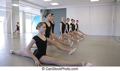 Young gymnasts sit on twine one by one in dancing class....