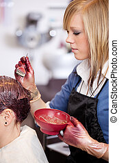 Pretty young female hairdresser or assistant applying a tint to a customers hair using a brush