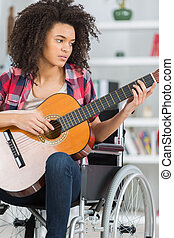 young handicapped guitarist woman sitting on wheelchair