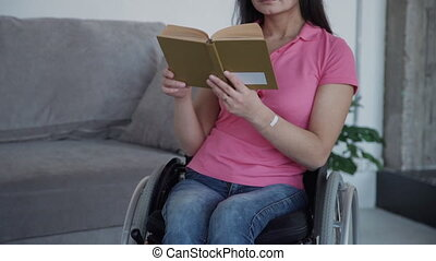 Young handicapped woman reading book sitting in wheelchair at home room. Front view of american disabled female holding literary work in hand, having recovery time in apartment. Concept: disability, interior, lifestyle.