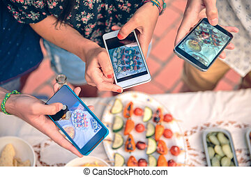 Young hands taking photos with smartphones to vegetable skewers