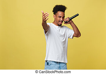 Young handsome African American Male Singer Performing with Microphone. Isolated over yellow gold background.