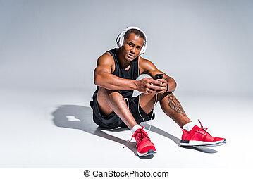 young handsome african american sportsman in headphones