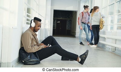 Young handsome african american student sitting on floor in...