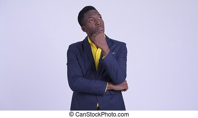 Young handsome African businessman in suit thinking