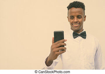 Young handsome African businessman using mobile phone against white background