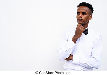 Young handsome African businessman wearing bow tie against white