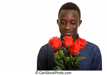 Young handsome African man holding red roses ready for Valentine