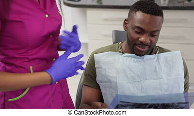 Young handsome african man patient sitting in dentistry chair and looking at the panoramic radiography, xray image of his jaws. Pretty african woman doctor explaining the ways of treatment