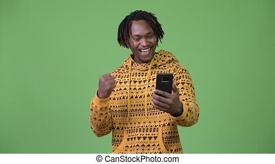 Young handsome African man using phone and getting good news...