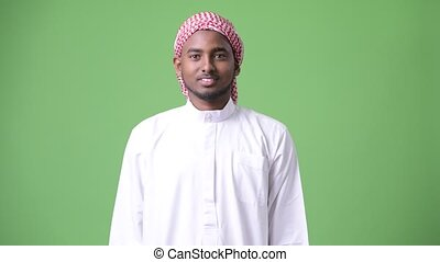 Young handsome African man wearing traditional Muslim...