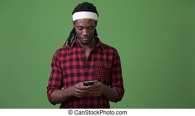 Young handsome African man with dreadlocks against green background