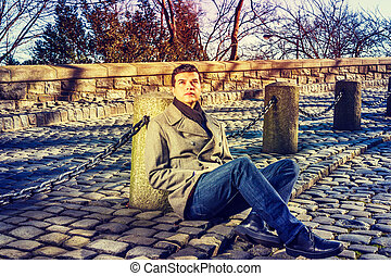 Young Handsome American Man relaxing at park in New York in winter