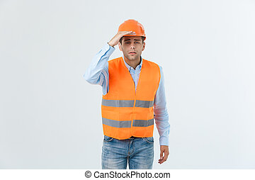 Young handsome architec man with wearing safety helmet over isolated background with hand covering head looking to something.