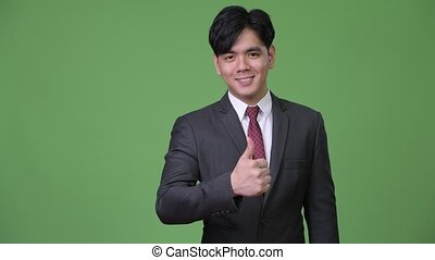 Young handsome Asian businessman giving thumbs up