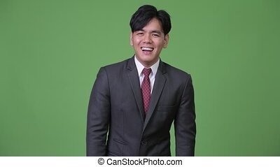 Young handsome Asian businessman laughing