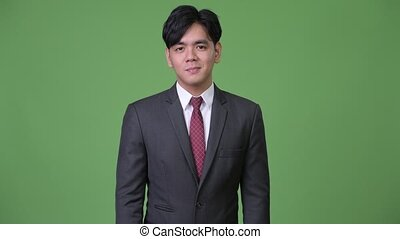 Young handsome Asian businessman nodding head yes - Studio...