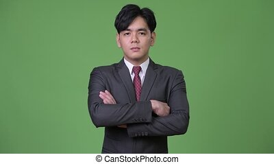 Young handsome Asian businessman with arms crossed